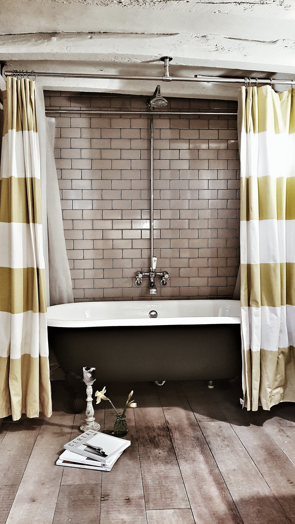 The yellow and white shower curtain that frames the roll top bath