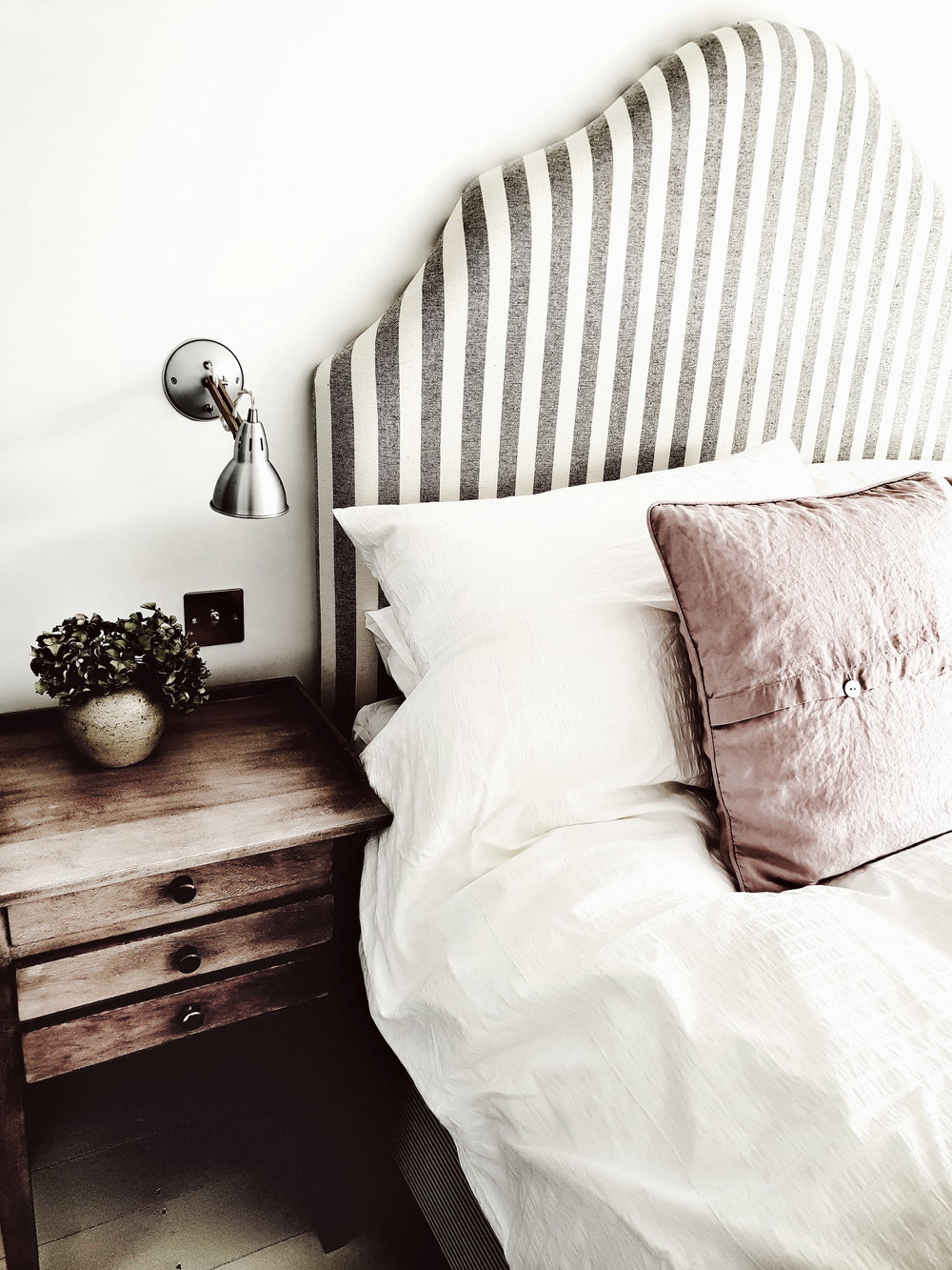 The upstairs ensuite bedroom with gorgeous striped headboard and exposed wooden beams