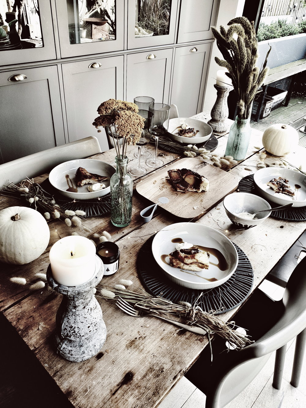 Pear Tarte Tatin served up on pale grey plates from Sainsbury's Home on a rustic wooden farmphuse table and set with vintage bottles and dried flowers for a modern rustic feel
