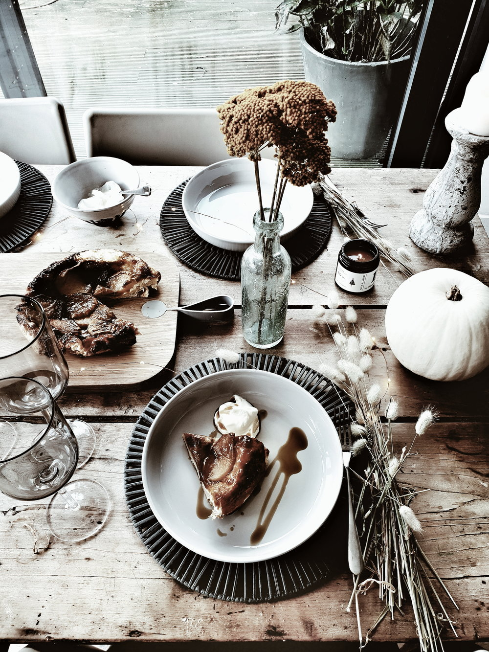 Pear Tarte Tatin served up on pale grey plates from Sainsbury's Home on a rustic wooden farmphuse table and set with vintage bottles and dried flowers for a modern rustic feel #farmhousekitchen #farmhousedecor #kitchentable #vintagekitchentable #autumnalstylingideas #autumnideas