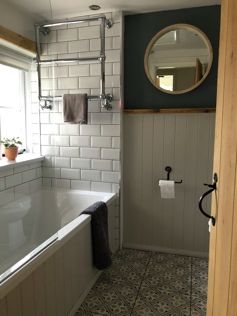 The blissful bathroom with patterned tile floor and a rather nice statement mirror
