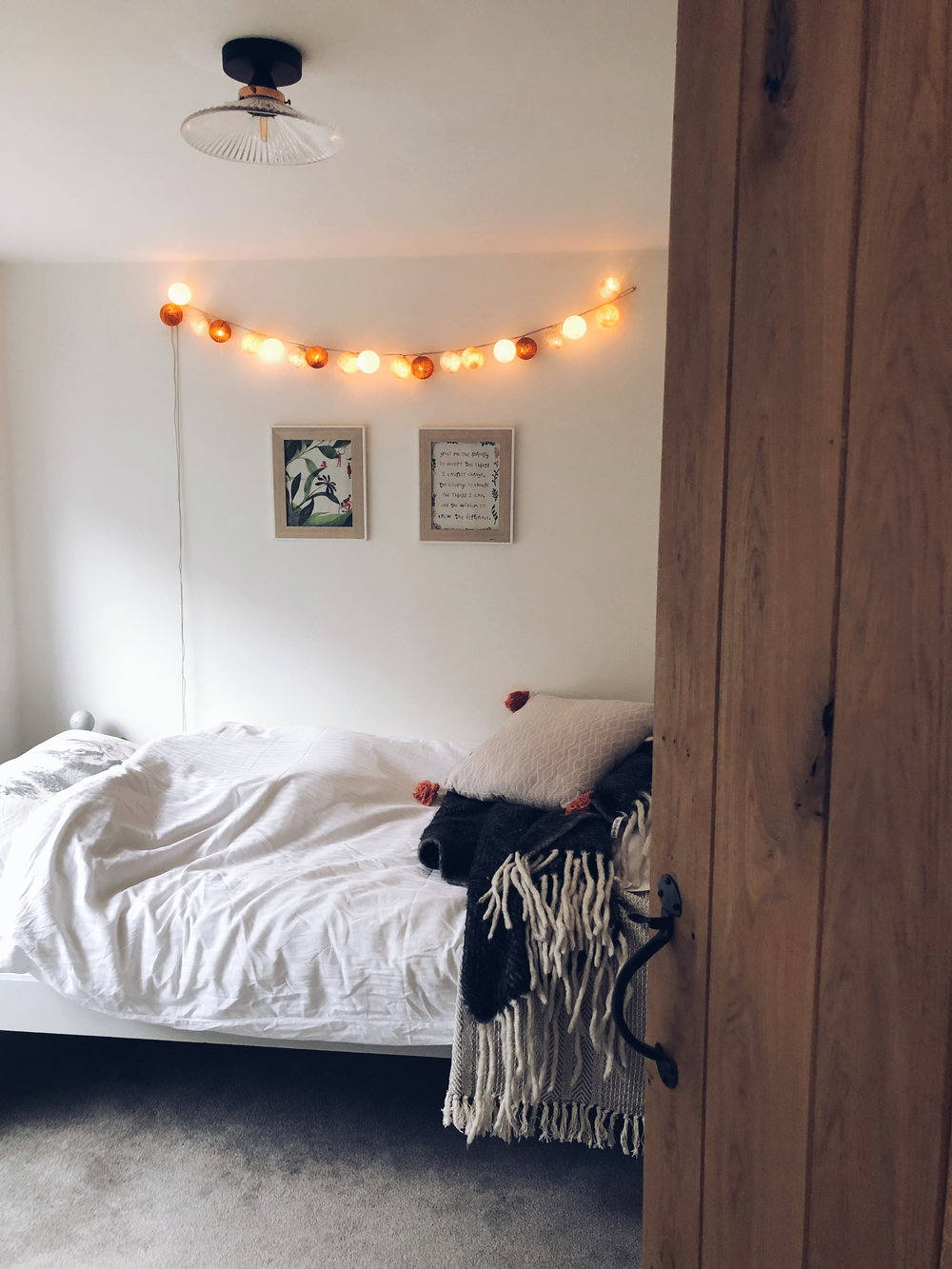 The simple white decor with hygge added fairy lights in one of the bedrooms