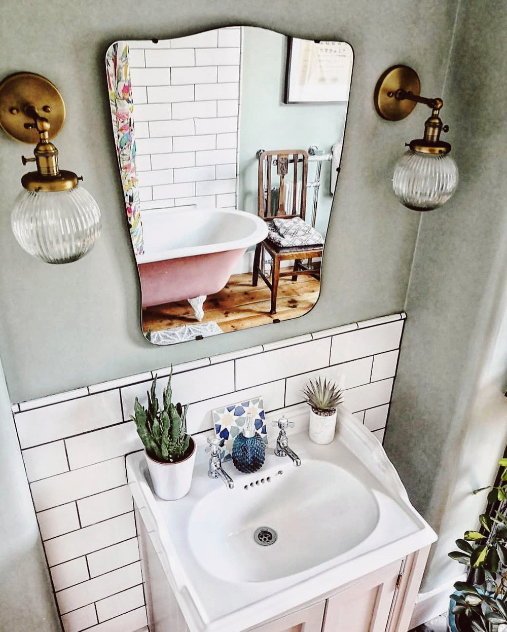 Pink freestanding rolltop bath reflected in a vintage mirror above a vanity unit