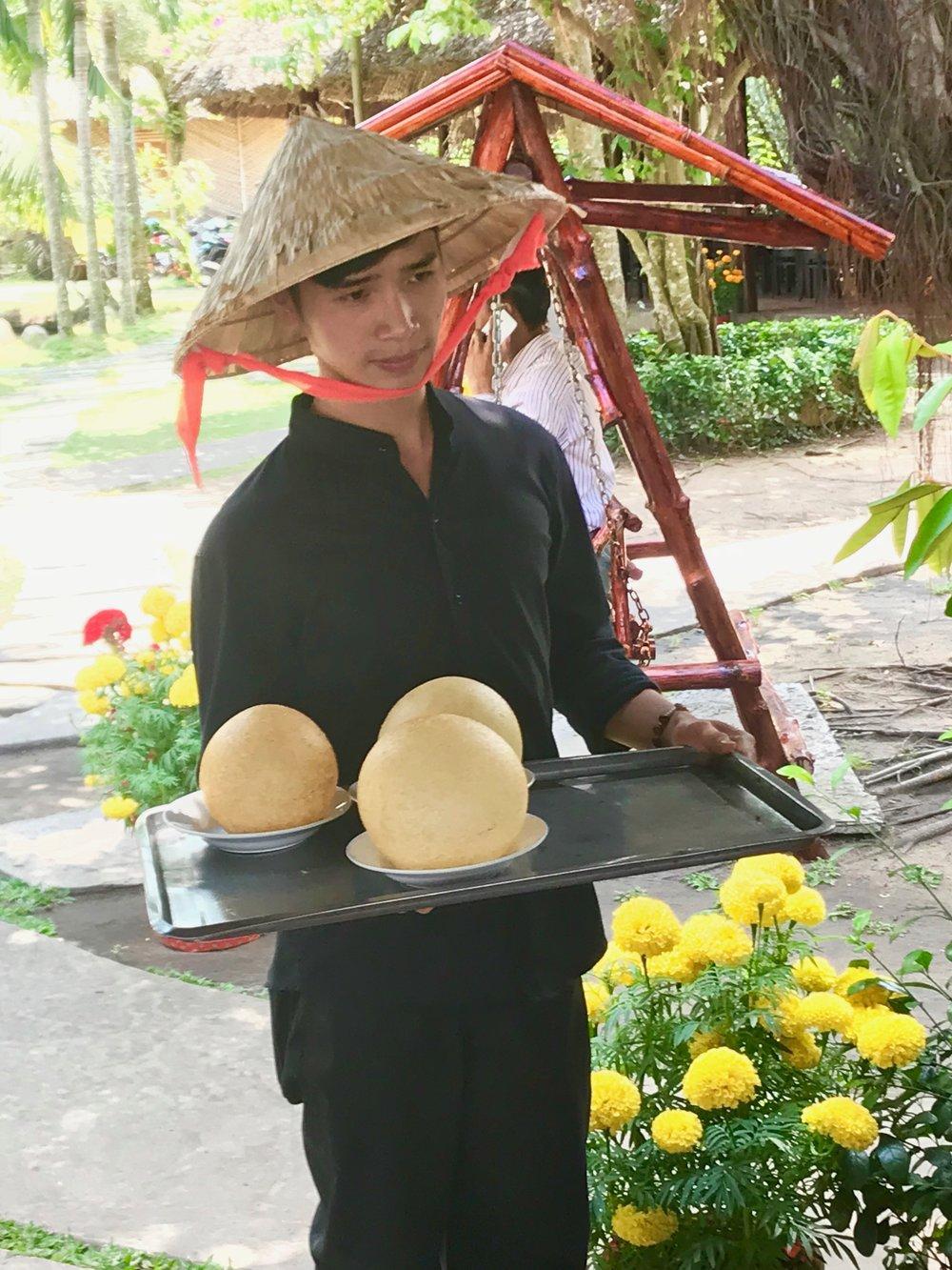 Waiter w Cone hat & globe sticky rice.jpg*.jpg
