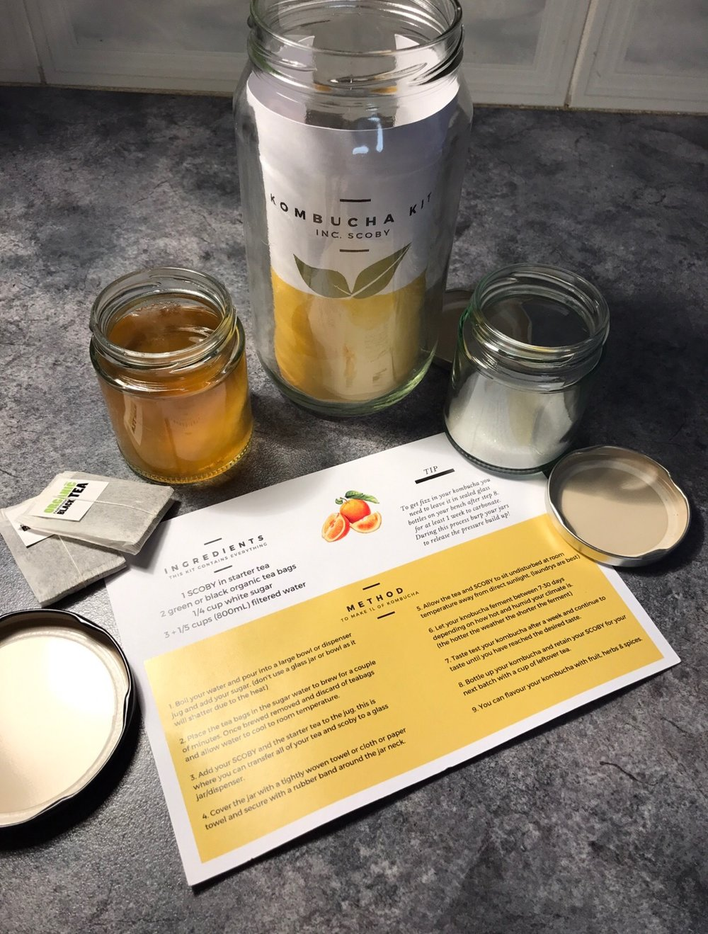 Kombucha Kit: note the SCOBY nor the sugar come in a little glass jar due to transport issues however you do receive a 1L mason jar to ferment in. The recipe card, organic tea, sugar, a kombucha SCOBY and a 1L glass mason jar.