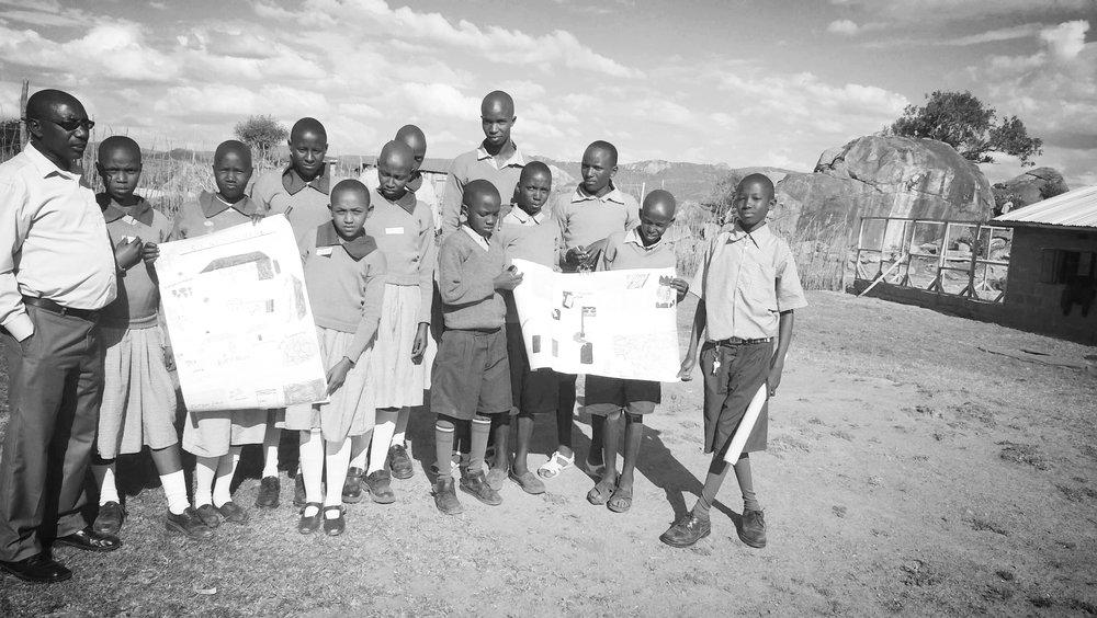 Children in ASAL region displaying their work.