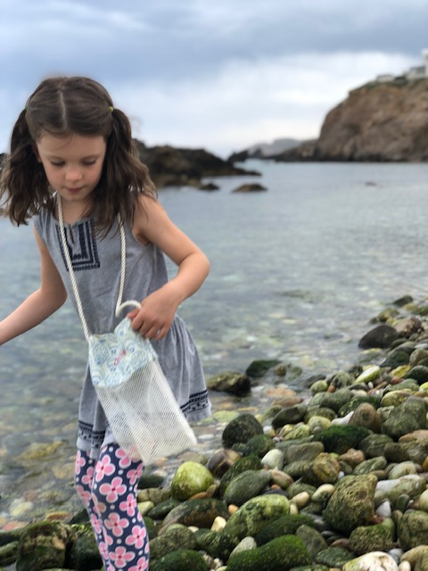 searching for sea glass on the rocky shore near the Portara