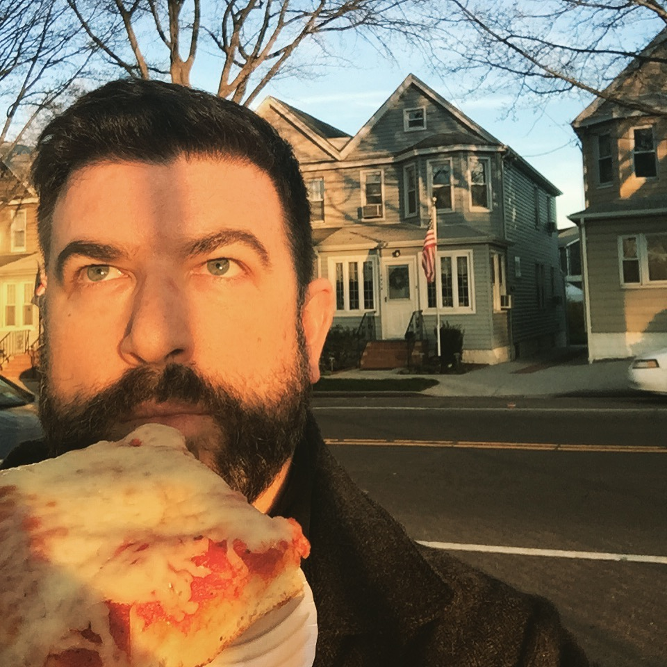 That's me eating a slice in front of the Bunkers' house (actually in Middle Village, Queens)
