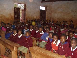 There are often 4 children to one desk at  Tloma Primary School