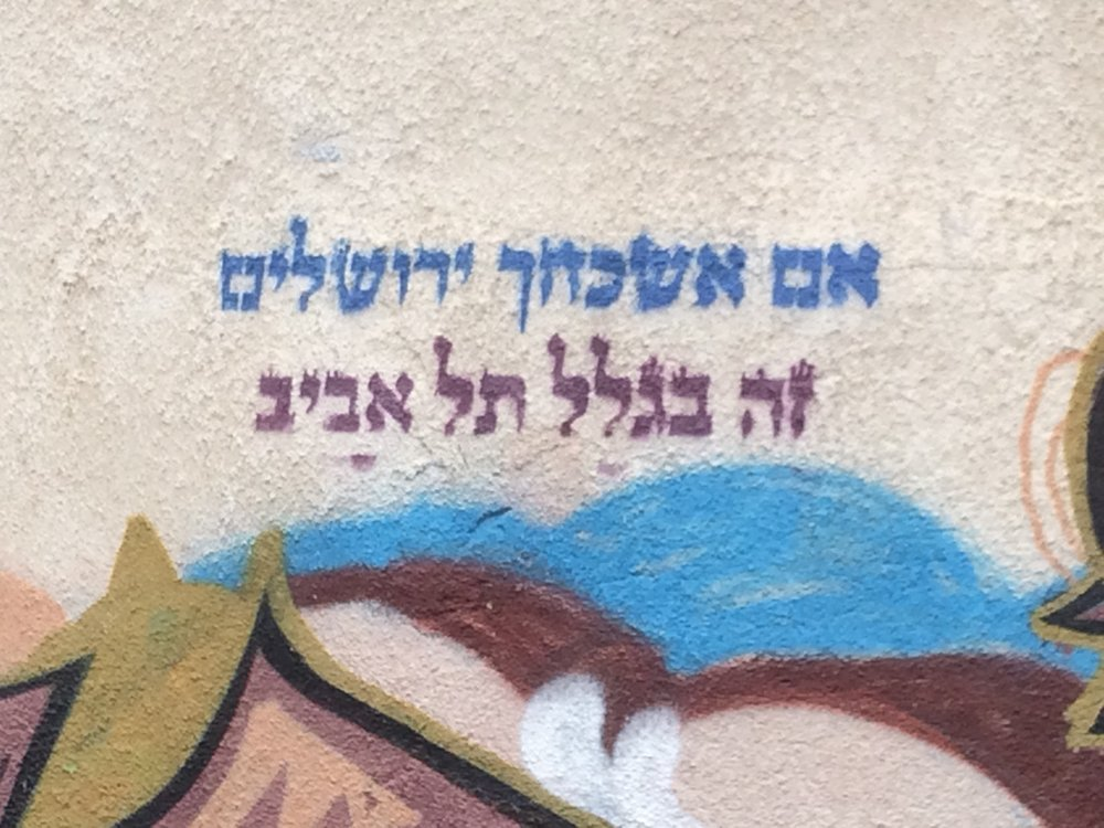 "My friend David Ackerman sent me this photo, a piece of street art or maybe even what some might call graffiti, from Florentin, a neighborhood in South Tel Aviv. That part of the city now enjoys a renaissance, a polite term for formerly not so nice areas which respectable middle-class people avoided, and which now command hefty prices for residential or commercial properties. This phenomenon includes adjacent Neve Tzedek and Yafo. This dynamic challenges many urban areas all over the world. Neighborhoods deteriorate: declining values, crime, drugs, poor schools, lack of commerce, joblessness, and a marked decline of the building stock. The poor get left behind, tied to the area by history and inability to leave.   Then often because of the prime location middle-class pioneers venture in, looking for bargains for themselves. Can these gentrifying neighborhoods manage to hold the older and newer more recent populations? This remains a question mark. The cities renew themselves: they get less dirty, more bright and shiny and fixed up, more prosperous, as populations shift within its confines, some people feeling like the winners, other like the losers.   Israel faces this challenge in its own unique way, given its history. Founded as a ""New Society"" in Herzl's vision it should and could be both socialist and capitalist, combining the virtues of fairness and freedom, equality and liberty, community and innovation. As Americans we often feel and appreciate the denseness of community life in Israel: the noticeable lack of privacy, the disregard of boundaries, the ways in which kids feel safe in the streets of their neighborhood, the person we barely know lending us a helping hand, and the like.   So the fact that Tel Aviv has become so expensive vexes Israelis. The city bustles, one hears and sees all of the construction and the new office buildings, suggesting the energy of the place, even as it partially conceals the reality that some Israelis feel left behind as others in the society race ahead. Some can afford to move up; others struggle not to fall farther down the ladder.  So this picture fills me with mixed emotions. ""If I forget thee, O Jerusalem..."" Psalm 137 intones, ""let my right hand forget its cunning."" The artist knows her Scripture. But then she continues ""That would be on account of Tel Aviv."" Maybe it's ok to choose Tel Aviv over Jerusalem, the new versus the old, Zionism over Judaism?   The pioneers who built the city named it Tel Aviv in honor of Herzl's utopian novel,  Oldnewland , the story of the Zionist building of its new society. They built the first modern Hebrew city. By that logic we should celebrate choosing Tel Aviv over Jerusalem, the present and future over the past of the Jewish people.   Choosing Tel Aviv over Jerusalem puts me in mind of the culturalist stream of Zionist thought, made famous by figures like Ahad Ha'am and Chaim N. Bialik. They fought not so much with the secular socialists as with their rabbinic forebears, who claimed Zionism either ought to be rejected as too modern and secular or made to fit into Torah Judaism. The culturalists insisted Jews and Judaism required regeneration, a new identity and a new culture (as opposed to religion), centering around the modernizing of the Hebrew language and the creation of modern literature and art.   Those sorts of thinkers and activists would have liked this piece of street art I think. Knowledge and love of Jewish tradition and Scripture, combined with the embrace of the new, expressed in a new form and a new space. As a Zionist writer put it, ""When someone comes and asks you, 'Where is your Jewish culture?' you will answer, 'What do you mean?' and take him through the streets of Tel Aviv."" (Marvin Lowenthal, ""This Hebrew Renaissance"" [1925])  - DBS"