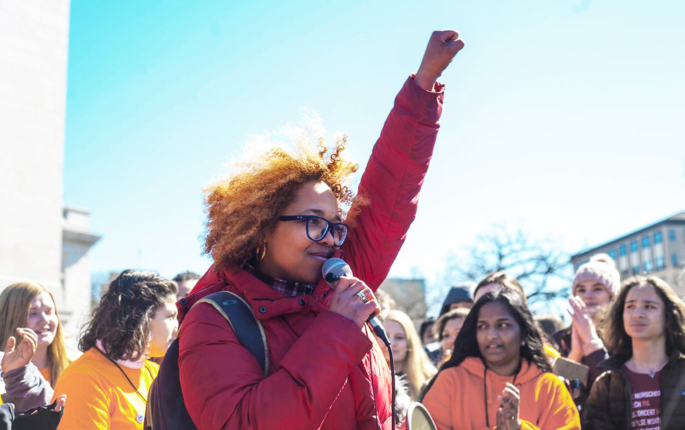 Ali speaking at the youth-led school walkout in 2017, where several thousand students from all over Wisconsin marched from Madison East High School to the Madison Capitol demanding gun control. Photo by Leslie Amsterdam.
