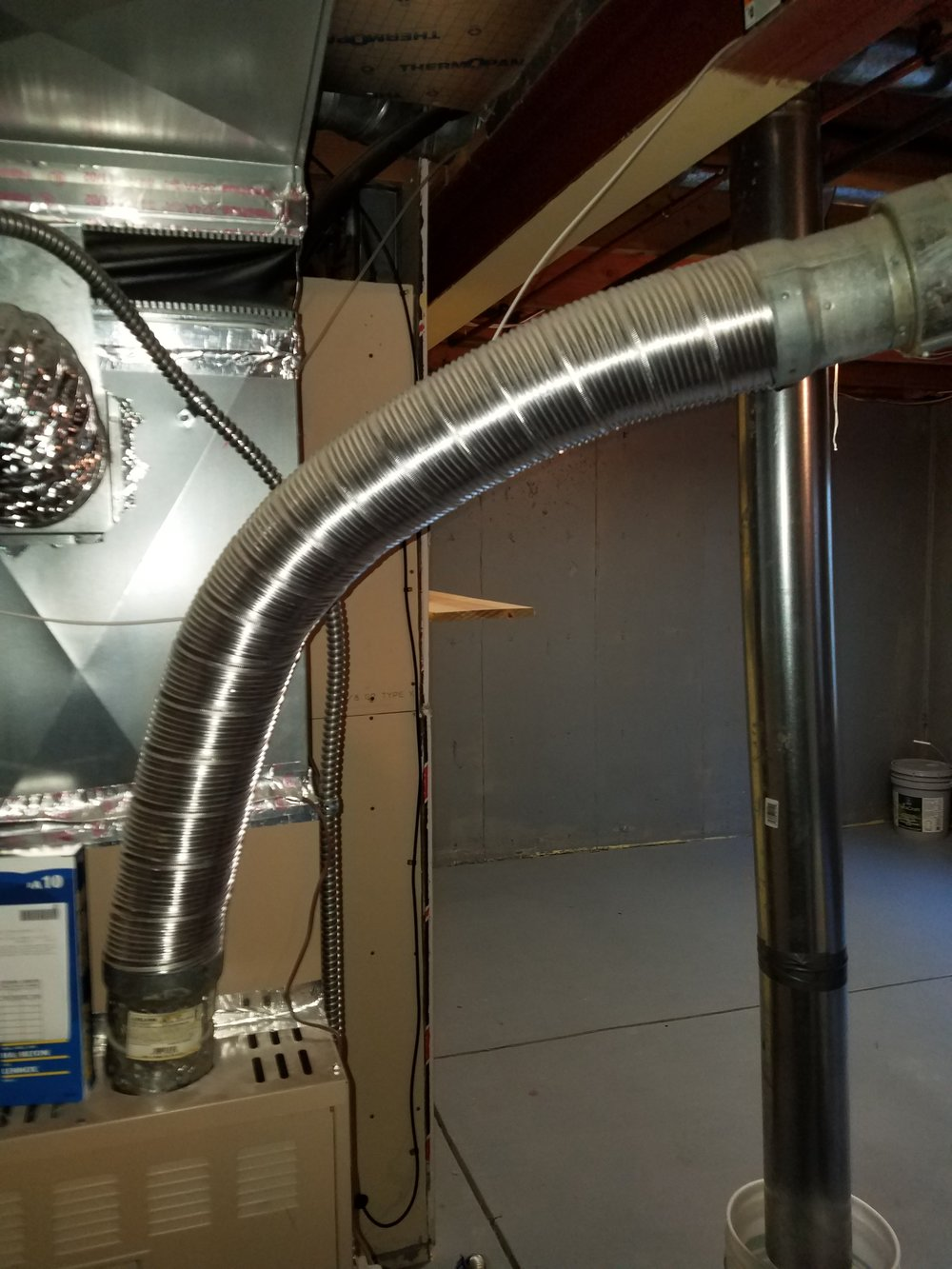 Although this flue may look questionable, there are several flexible flue connections that are safe to use at water heaters, furnaces and boilers.