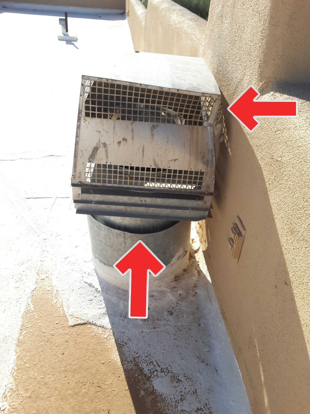 This poorly planned fireplace flue cap is against the parapet wall and has large gaps allowing water entry into chimney chase.