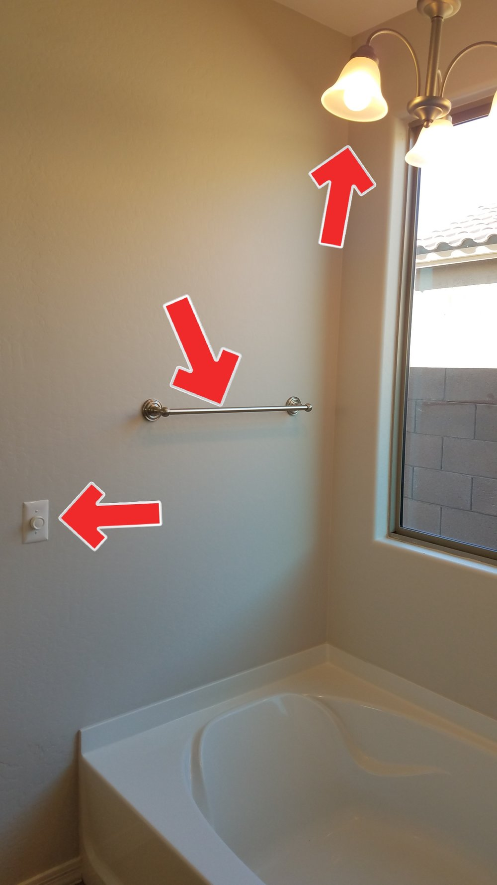 A hanging light fixture over a tub, a switch within 3' of tub and a towel bar that might be mistaken for a handrail. Many hazards, terrible planning.