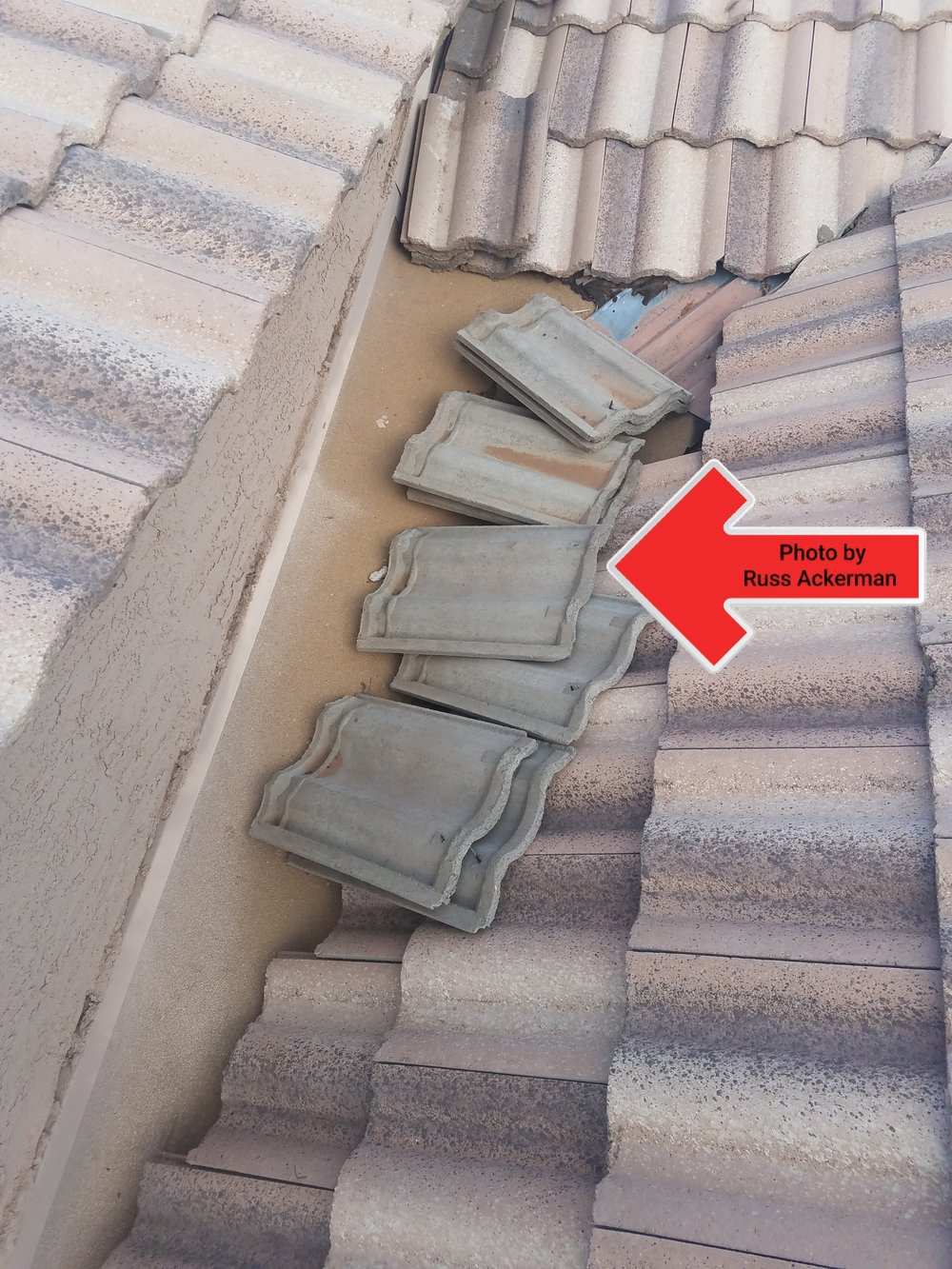 It's a great idea to have extra roof tiles, but storing them on the roof is a potential safety hazard and will cause damage to an asphalt roof valley.