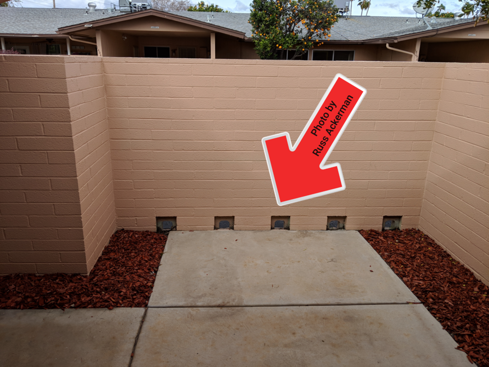 Drainage holes are important and often missing when a patio is surrounded by a block wall.