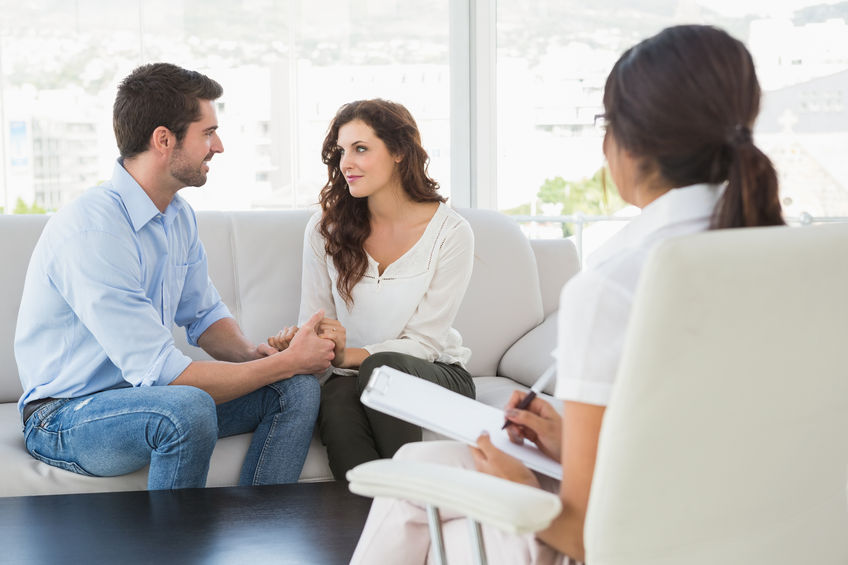 46208401-reconciled-couple-smiling-at-each-other-in-the-therapist-office.jpg