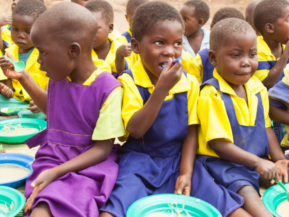 "Children in Malawi eating ""VitaMeal"" while attending school"