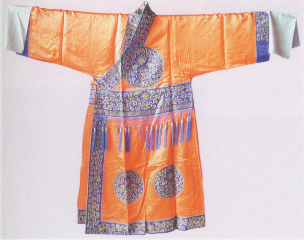Eunuch Robe  Costume,   worn by eunuchs. There are two types of eunuch robes: small and big (not referring to the size, but the wearer's importance).  The small one is distinguished by its slanting collar and buttons on the right ( dajin ). It comprises the upper part ( shagnyi ) and the lower part ( xiajiao ). The hem of the lower part is slightly wider than the upper's. The cuffs and waist part also have about three-inch wide helms. All the helms are embellished with patterns of frets and dragons. There are dragons in round-frame that is seven to eight inches in diameter on the front, the back and sleeves, respectively. Characters like the four eunuchs wear the small ones in  The Hall of Eternal Youth .  The big robe is marked by round neck with trimmed collar. Its bottom parts are embroidered with patterns of sea waves, slender dragons, or dragons in round frame. Other details are similar to those of small eunuch robes. The big type is worn by the eunuch supervisor or the eunuchs with names in the play.