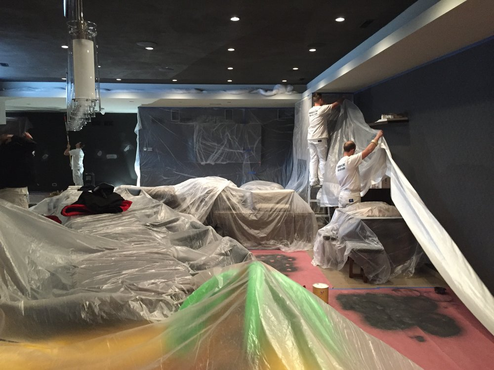 Painters Inc crew protects furniture with plastic tarps before beginning painting the interior walls of a restaurant.