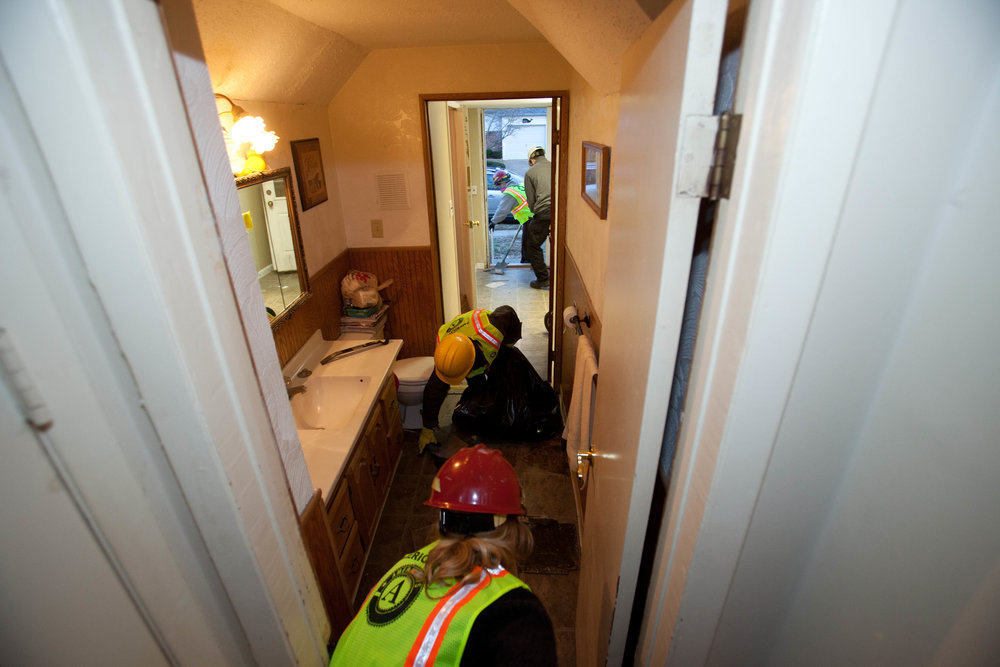 AmeriCorps members from the Washington Conservation Corps and AmeriCorps St. Louis removing tile from a home damaged by hurricane Sandy in Union Beach, NJ. Corporation for National and Community Service Photo.