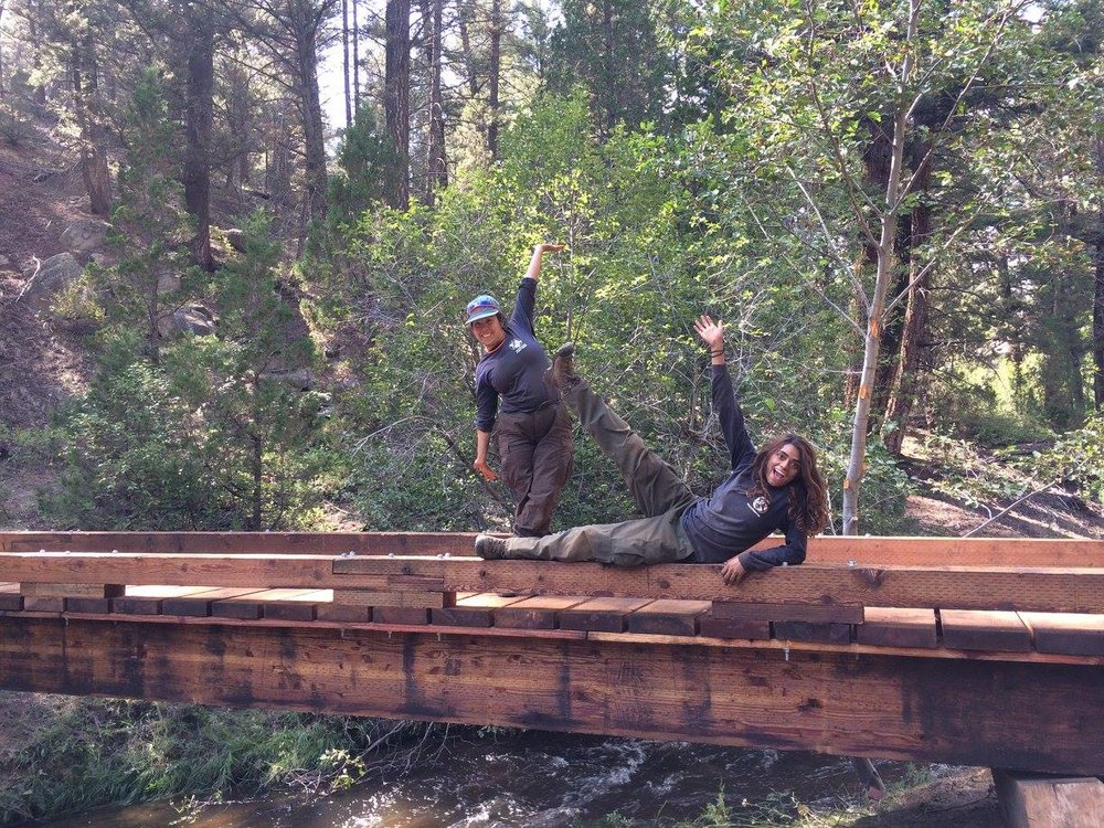 Year 22 & 23 members, Brittany Merriman and Chandni Patel, pose on a completed bridge construction in Pipestone Pass, Montana, 2017. The bridge was constructed to mitigate recreational activity crossing the stream that was disturbing an endangered species of trout.