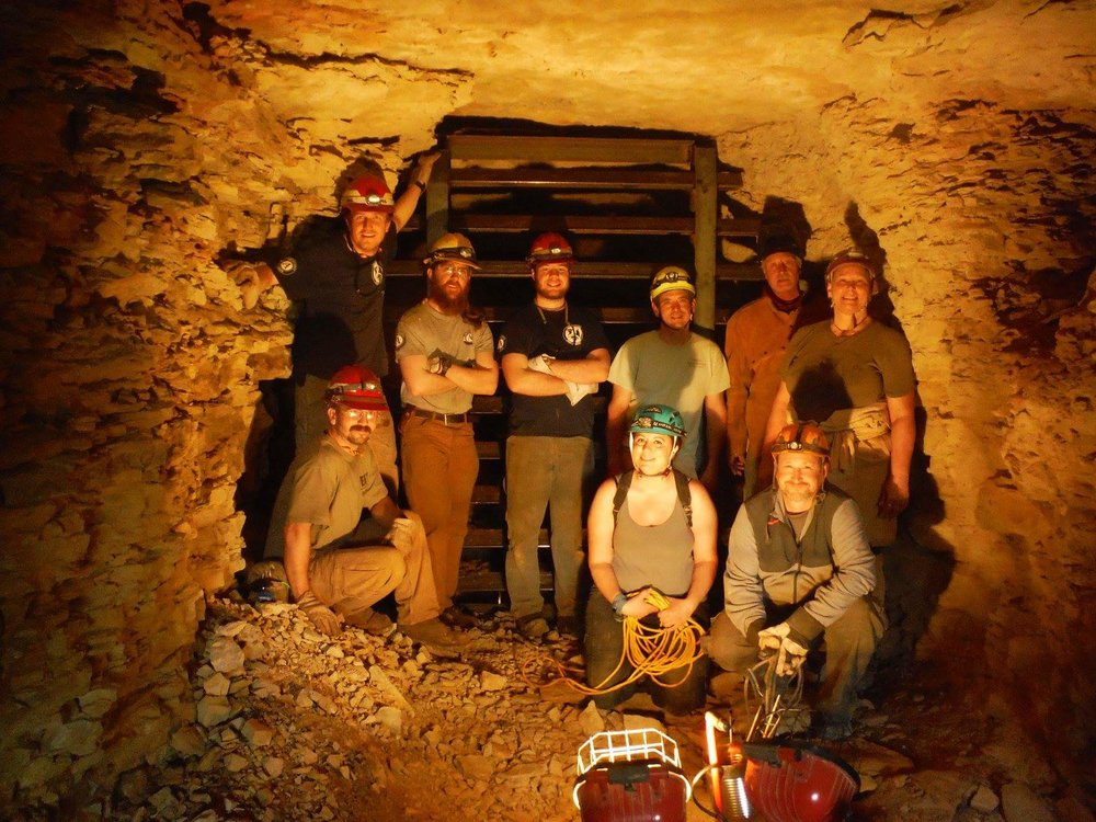Nick Maya (Left, standing) with AmeriCorps Members Andy Clubb (Left sitting), Sam Owens (Center, yellow helmet), and Colin Wilson (center), with members of the Cave Research Foundation, pose in front of a completed bat cave gate. These gates and built to allow bats to safely enter and exit their roosts but prohibit humans from disturbing their habitat and spreading the deadly white nose syndrome.