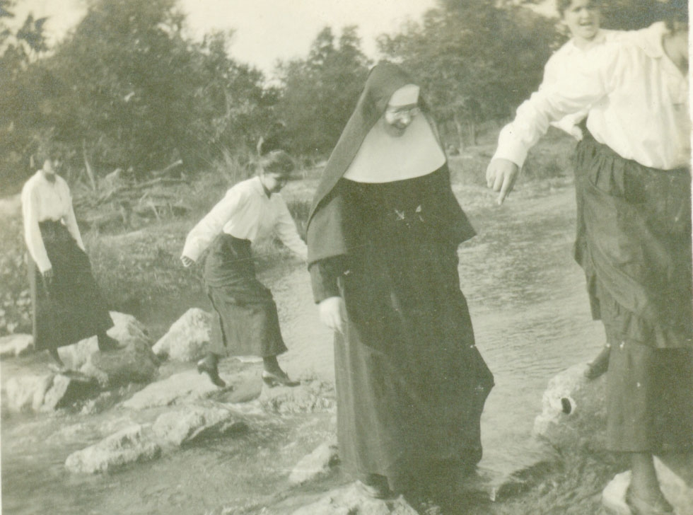 Sr Alacoque walking across river rocks.jpg