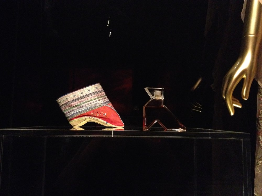 "Left: shoe, Chinese, 1800–1943 (courtesy the Metropolitan Museum of Art, Gift of Mrs. Robert Woods Bliss, 1943); right: ""La Fille de Roi de Chine"" flacon perfume bottle, Callot Soeurs (1923) (courtesy Christie Mayer Lefkowith) (photo by the author for Hyperallergic)"