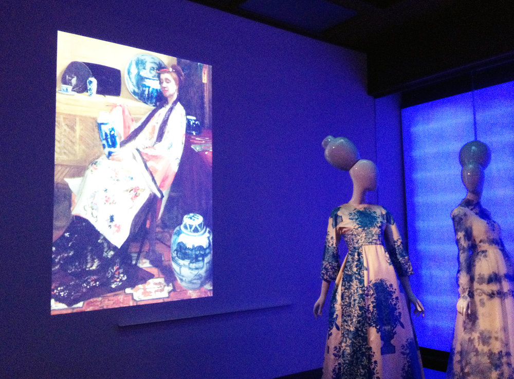 "From left to right: projected image of James McNeill Whistler's 1864 painting ""Purple and Rose: The Lange Leizen of the Six Marks""; Valentino, ""Blue Willow Gown"" (1968) (photo by the author for Hyperallergic)"