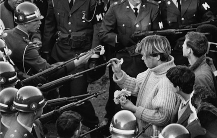 George Edgerly Harris II (AKA Hibiscus) placing a flower in the gun of a soldier, October 1967 (photography by Bernie Boston, via Wikipedia)