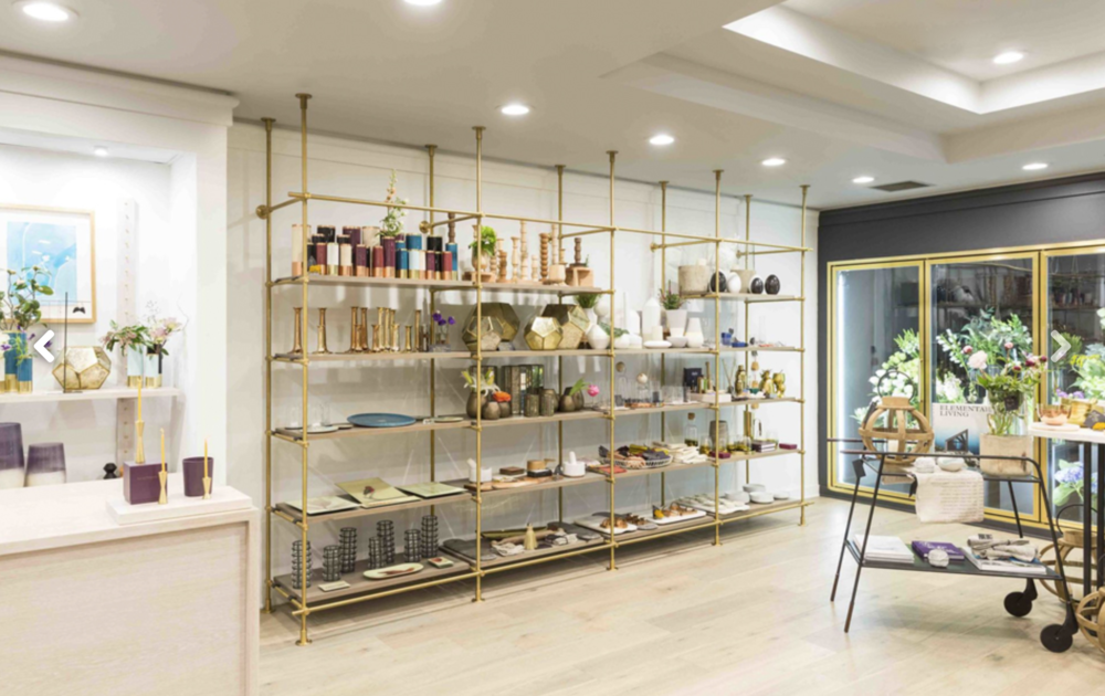 In this Philadelphia boutique, Amuneal's brass and silvered-oak Collector's shelving unit is used to show off merchandise. Custom designed for the space, the unit includes several flexible display options. Photo by Goldenberg Photography