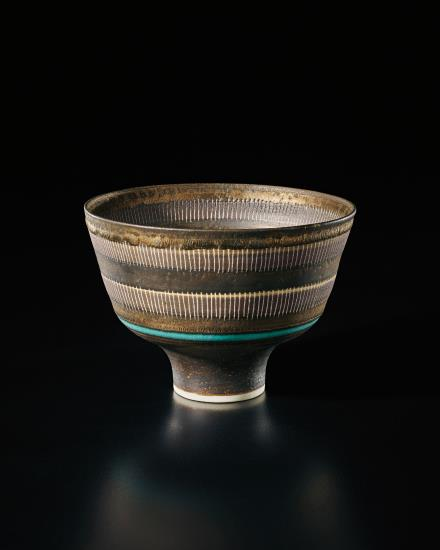 Straight-sided bowl, circa 1978, by Lucie Rie. Porcelain, golden manganese glaze, two terracotta bands crossed with vertical sgraffito lines, terracotta well and a turquoise ring. 4 3/8 in. high, 5 7/8 in. diameter. Impressed with artist's seal. Courtesy of Phillips.