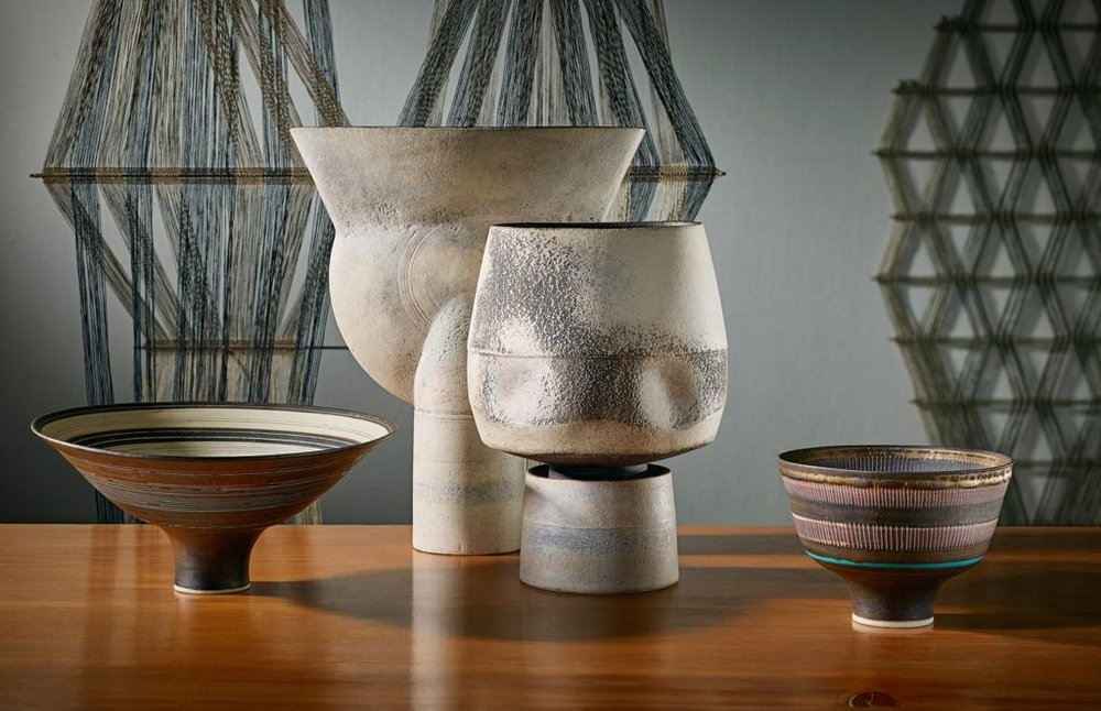 Ceramics by Lucie Rie (on left and right sides) and Hans Coper (in center) with a woven textile by Peter Collingwood (background). Courtesy of Phillips.