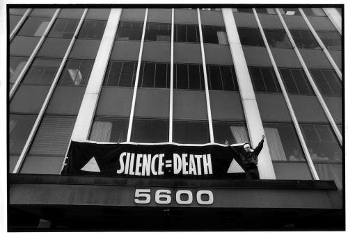 "ACT UP , October 11, 1988; photograph of ACT UP raises SILENCE = DEATH banner on the Food and Drug Administration (FDA) offices protesting the slow drug approval process. Scene from ""How to Survive a Plague,"" directed by David France"