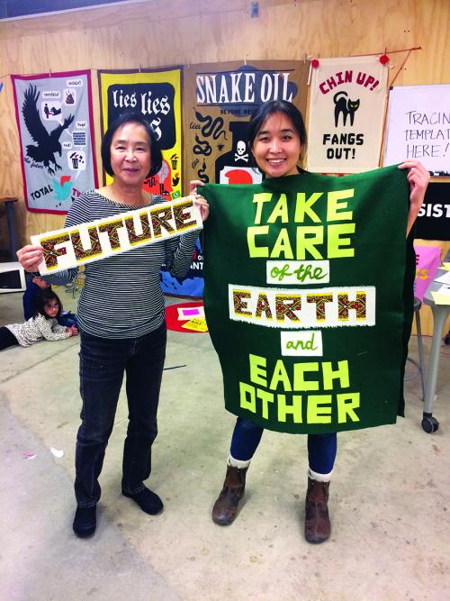 "Artist Thi Bui (right) and her mother hold up the banners they collaboratively made during ""Reap What You Sew"" held at UC Berkeley. Sponsored by Someday Is Now, an artist collective of UC Berkeley students, staff, and faculty. Prepared in the lead-up to the Presidential Inauguration, these banners were used during the Women's Marches across the United States. January 13, 2017.Courtesy of Stephanie Syjuco"