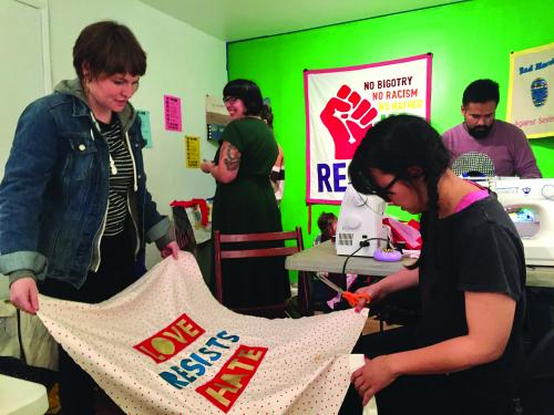 """Reap What You Sew,"" banner making workshops led by Stephanie Syjuco. Hosted by 100 Days Action at Royal Nonesuch Gallery, Oakland, California, January 8, 2017. Pictured: Artist participants finishing their projects. Courtesy of Ken Lo"