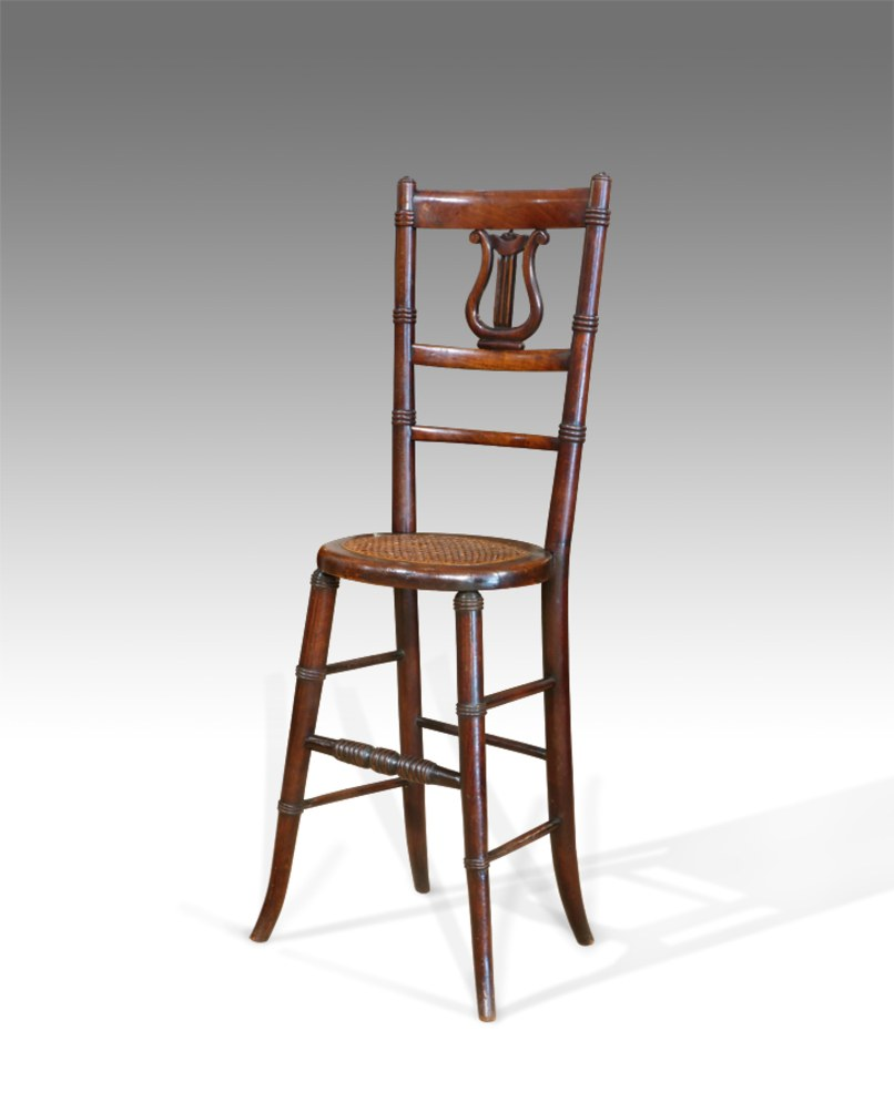 A Victorian deportment chair with a caned seat and a carved lyre-shaped splat.  Thakeham Furniture , Petworth, U.K. Courtesy of Thakeham Furniture