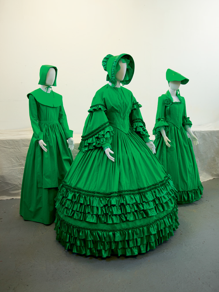 FIG. 6 –  Left to right,  The Visible Invisible: Plymouth Pilgrim (Simplicity) , 2018, cotton muslin chromakey back- drop fabric, ribbon, lace, buttons, and display form;  Antebellum South (Simplicity) , 2018, cotton muslin chromakey back- drop fabric, polyester satin, crocheted cotton, ribbon, lace, buttons, and display form;  Colonial Revolution (McCall's) , 2018, cotton muslin chromakey back- drop fabric, ribbon, lace, buttons, and display form. All collection of the artist