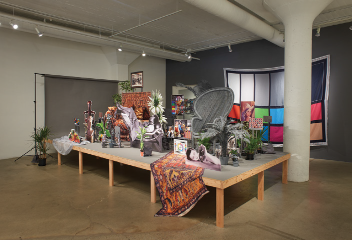 FIG. 11 – Neutral Calibration Studies (Ornament + Crime) , 2016, wooden platform, neutral grey seamless backdrop paper, digital adhesive prints on laser-cut wooden props, dye-sublimation digital prints on fabric, items purchased on eBay and craigslist, photographic prints, artificial and live plants, and neutral calibrated gray paint. Collection of the artist and Nion McEvoy