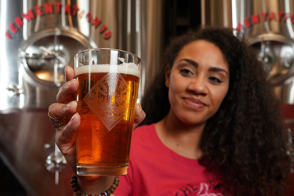 Hazel holding a pint of beer in the brewery