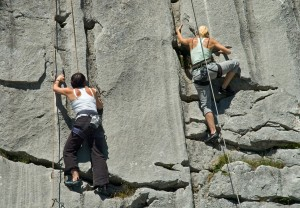 Two female rock climbers climbing limestone in Switzerland