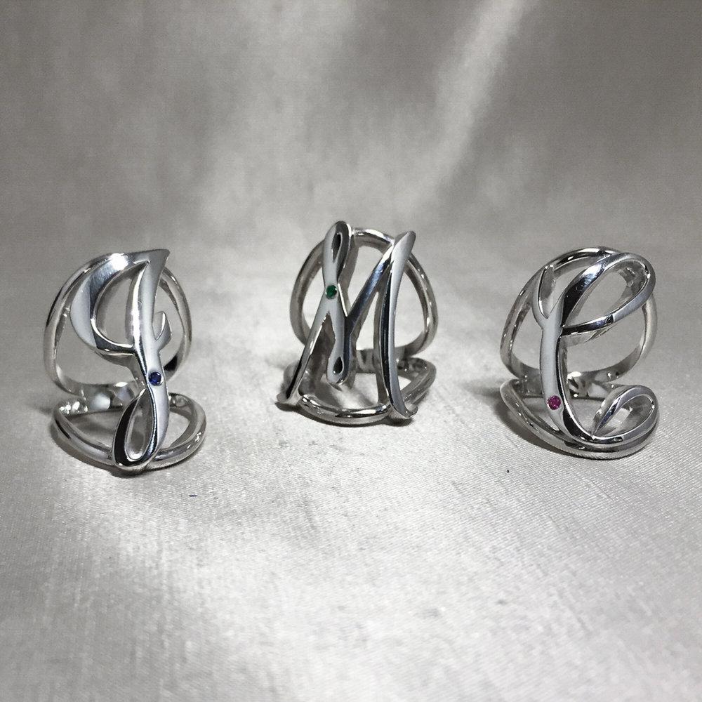 Custom Initial Rings with Birthstone Gems.