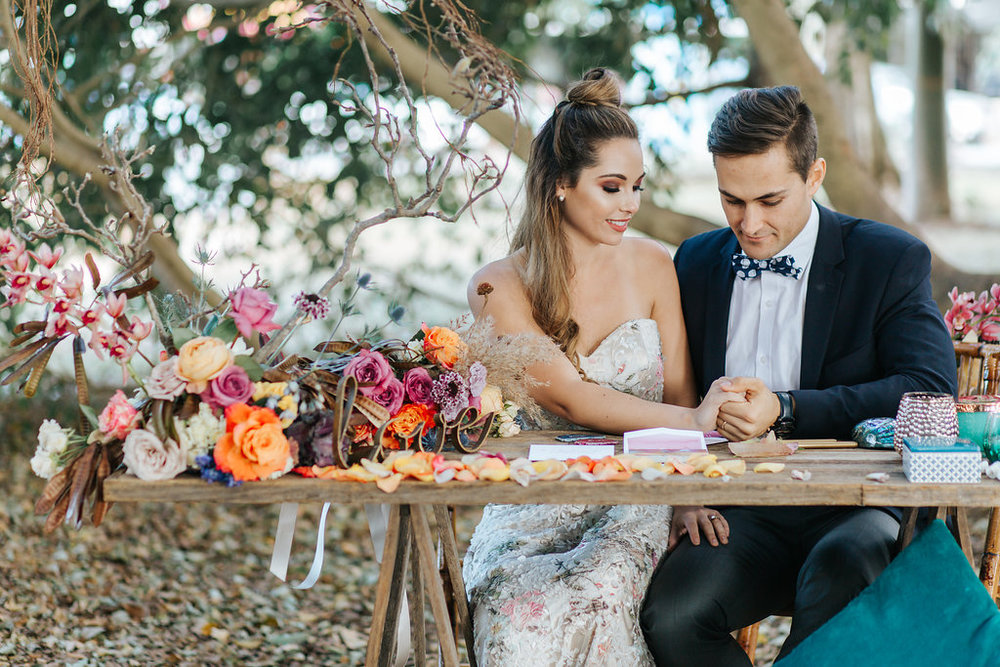 Bloodwood Botanica | Bohemian bright wedding signing table flowers