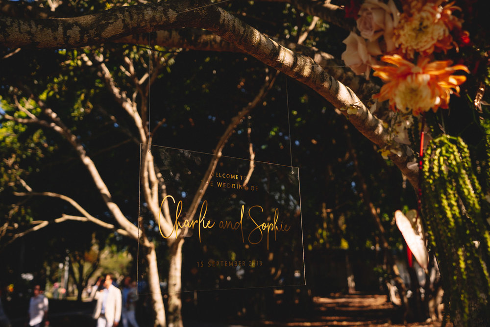 Bloodwood Botanica | Noosa waterfront pink and orange wedding flowers welcome sign