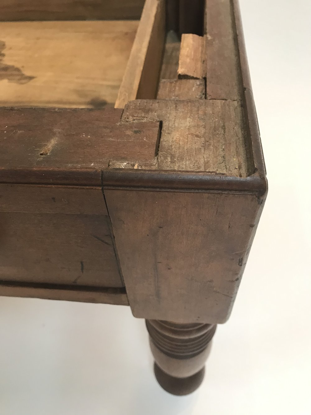 Base of cherry sugar chest showing perimeter molding, note how the top piece of wood above the drawer is dovetailed in to the top of the front leg.