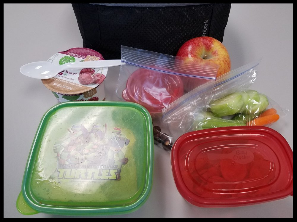 The contents of my lunchbox one day this past week - (PB&J sandwich, chips, veggies with hummus, yogurt, apple and a few mini peanut butter cups).