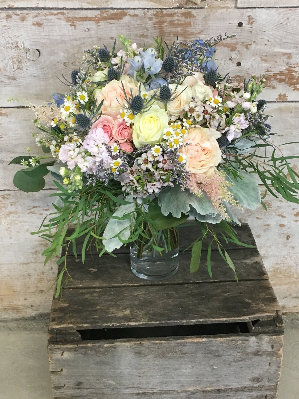 Garden roses, a variety of fillers, and a touch of whimsy eryngium (aka thistle) were perfect for a secret garden wedding theme!