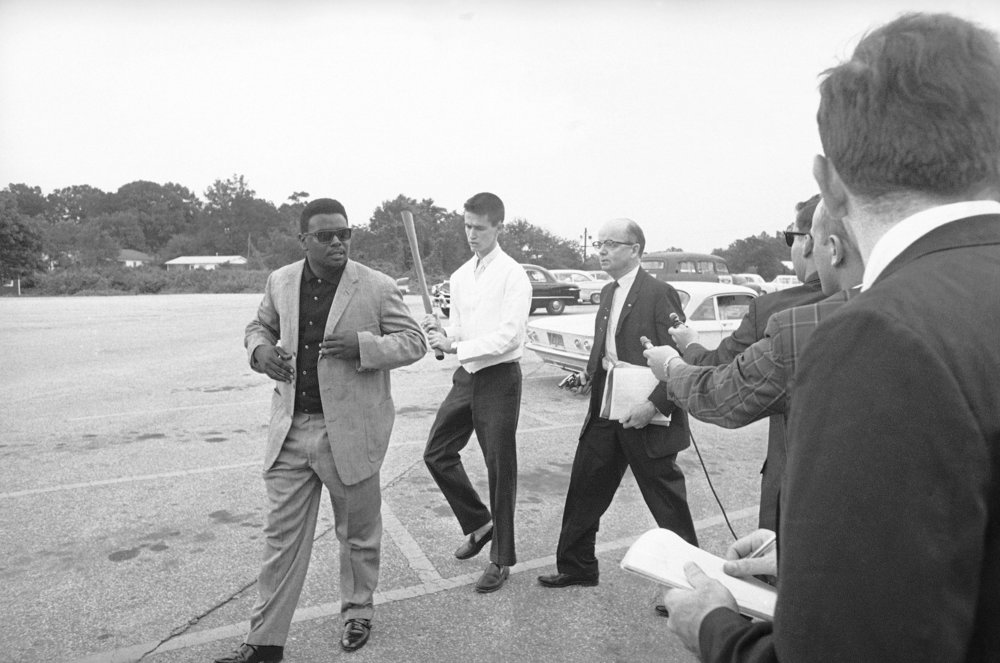 PAGE 86: THE DAY FOLLOWING THE SIGNING OF THE CIVIL RIGHTS ACT OF 1964 BY PRESIDENT LYNDON B. JOHNSON, REVS. GEORGE WILLIS JR., WOODROW T. LEWIS, AND ALBERT L. DUNN ATTEMPTED TO INTEGRATE THE PICKRICK RESTAURANT OWNED BY STAUNCH SEGREGATIONIST LESTER MADDOX. THE THREE MEN WERE DENIED SERVICE AND SHOVED OUT OF THE RESTAURANT. AN ASSOCIATED PRESS PHOTOGRAPHER CAPTURED REV. WILLIS JR. (LEFT) WALKING TO HIS CAR FOLLOWED BY MADDOX, POINTING A SHORT PISTOL, AND HIS SON HOLDING AN AX HANDLE (PERMISSION OF THE ASSOCIATED PRESS).