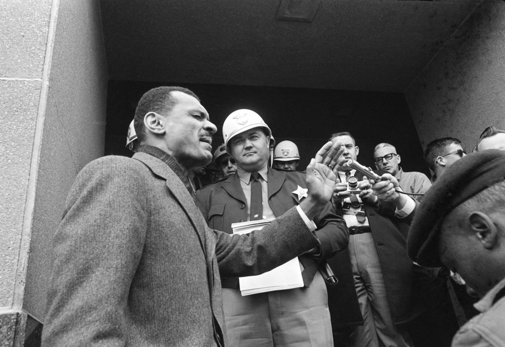 PAGE 89: IN JANUARY 1965, SCLC DIRECTOR REV. C.T. VIVIAN LED A GROUP OF DEMONSTRATORS IN PRAYOR AS THEY ATTEMPTED TO ENTER THE DALLAS COUNTY  COURTHOUSE TO REGISTER TO VOTE. DEPUTY SHERIFF JIM CLARK STRUCK REV. VIVIAN DURING A NATIONALLY TELEVISED PROGRAM (PERMISSION OF THE ASSOCIATED PRESS).